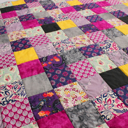 Modern patchwork quilt in purple and berry tones