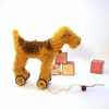 little Airedale terrier on vintage Meccano wheels