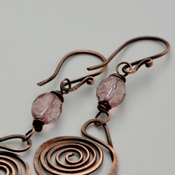 Copper spiral earrings with pink glass.