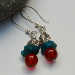 Sterling silver earrings with orange and blue gemstones and a silver spiral.