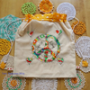 Drawstring bag with appliqued peace symbol