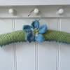 Hand knitted padded coat hanger with knitted anemone flower