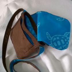 Small dark brown canvas cross-body bag with turquoise lining and pockets