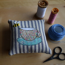 Blue ticking pincushion with an embroidered bee and Liberty teacup and saucer.
