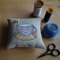 Linen pincushion with an embroidered bee and Liberty teacup and saucer.