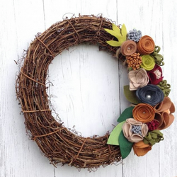 Grapevine wreath decorated with handmade felt flowers in Autumn colors