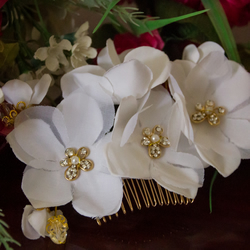 Gold hair comb decorated with white flowers
